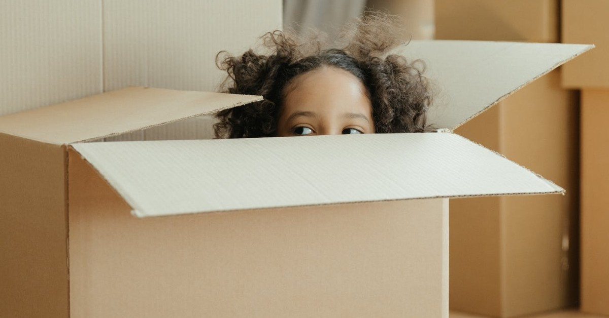 young girl inside cardboard box